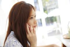 Азиатская молодая женщина вызывая говорить на callephohe телефона в coffeeshop стоковое фото