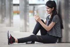 азиатская молодая женщина фитнеса принимая перерыв после разминки работая используя смартфон на улице в городском городе остатки  стоковая фотография
