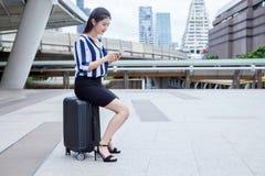 азиатская молодая коммерсантка сидя на багаже используя смартфон стоковое изображение