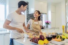 Азиатская молодая пара смотрящ и усмехающся пока варящ в kitch Стоковые Фото