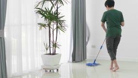 Азиатская молодая семья помощи мальчика убирая дом используя mop видеоматериал