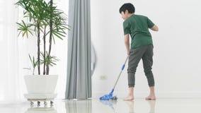 Азиатская молодая семья помощи мальчика убирая дом используя mop сток-видео