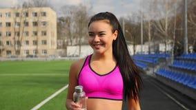 Азиатская молодая sporty девушка с бутылкой воды в руках идет на стадион после тренировки акции видеоматериалы