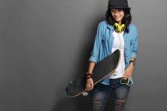 Азиатская молодая девушка конькобежца держа скейтборд Стоковое Изображение RF