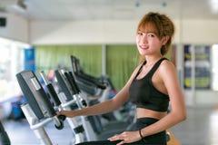 Азиатская молодая женщина в носке спорта делая спорт в спортзале Стоковое Фото