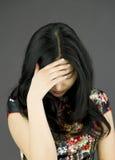 Азиатская молодая женщина пряча ее сторону стоковая фотография