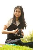 Азиатская молодая женщина сидит на биноклях насыпи ища Стоковые Изображения