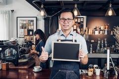 Азиатская мужская рисберма демикотона носки barista thumbs вверх на пустом классн классном стоковая фотография rf