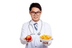 Азиатская мужская улыбка доктора с красными яблоком и картофельными стружками Стоковые Изображения