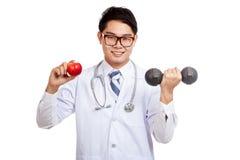 Азиатская мужская улыбка доктора с красным яблоком и гантелью Стоковое Изображение