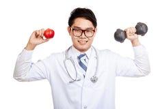 Азиатская мужская улыбка доктора с красным яблоком и гантелью Стоковые Изображения