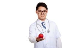 Азиатская мужская улыбка доктора с красным яблоком Стоковое фото RF
