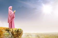 Азиатская мусульманская женщина в вуали подняла руки и молить на краю скалы стоковые изображения