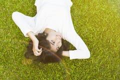Азиатская ложь молодой женщины на траве Стоковое Изображение RF