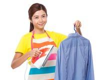 Азиатская домохозяйка используя утюг пара на рубашке Стоковые Изображения