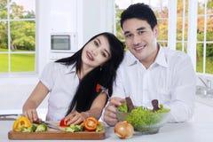 Азиатская пара делает салат в кухне Стоковая Фотография RF