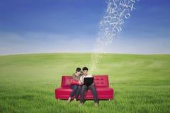 Азиатская пара используя компьтер-книжку с летанием помечает буквами напольное Стоковая Фотография RF