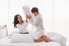 Азиатская пара сидит на кровати, они имеет бой подушками стоковая фотография