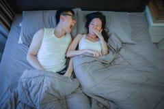 Азиатская пара с плохим дыханием выдает на кровати на ноче Стоковое Фото