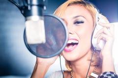 Азиатская певица производящ песню в студии звукозаписи Стоковая Фотография RF