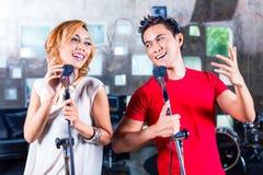 Азиатская певица производящ песню в студии звукозаписи стоковая фотография