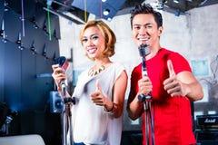 Азиатская певица производящ песню в студии звукозаписи стоковые изображения