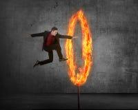 Азиатская персона дела скача через кольцо огня Стоковые Изображения RF