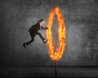 Азиатская персона дела скача через кольцо огня Стоковое Изображение