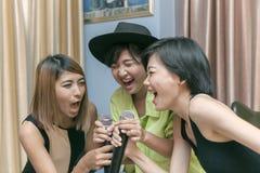 Азиатская песня караоке петь более молодой женщины с стороной счастья стоковая фотография
