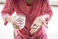 Азиатская пожилая женщина принимающ и ела медицины и витамины стоковое фото rf