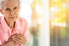 Азиатская пожилая женщина с некоторыми симптомами, затруднением дыша, страданием или проблемами сердца, связывает симптомы сердца стоковое изображение rf