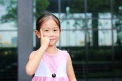Азиатская позиция маленькой девочки указывая ее forefinger вверх с меньшей улыбкой стоковые фото