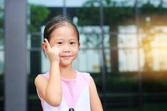 Азиатская позиция маленькой девочки указывая ее forefinger вверх с меньшей улыбкой стоковое фото rf