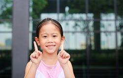 Азиатская позиция маленькой девочки указывая ее forefinger вверх с меньшей улыбкой стоковое изображение