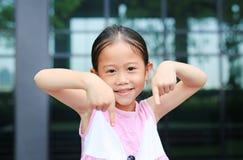 Азиатская позиция маленькой девочки указывая ее forefinger вниз с меньшей улыбкой стоковые изображения rf