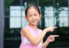 Азиатская позиция маленькой девочки указывая ее forefinger рядом с с милой улыбкой стоковое изображение