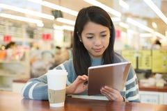Азиатская польза молодой женщины ПК таблетки с чашкой кофе Стоковое Изображение RF