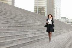 азиатская прогулка бизнес-леди возникновения вдоль говорить лестниц стоковое фото