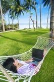 Азиатская работа девушки в гамаке с компьтер-книжкой на пляже Стоковое Изображение RF