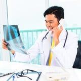 Азиатская рентгенограмма диагноза доктора внутри практикует Стоковые Фотографии RF