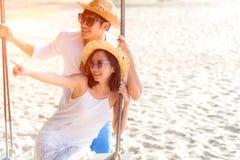 Азиатская романтичная пара сидит на пляже моря на качании веревочки ослабляет и счастье на праздник Стоковые Фото