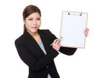Азиатская ручка коммерсантки пишет на доске сзажимом для бумаги Стоковая Фотография
