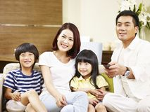 Азиатская семья при 2 дет смотря ТВ дома Стоковое Изображение