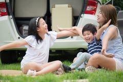 Азиатская семья сидя в парке стоковые изображения rf