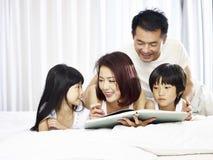 Азиатская семья с книгой чтения 2 детей в кровати Стоковые Фото