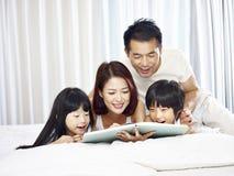 Азиатская семья с книгой чтения 2 детей в кровати Стоковое Фото