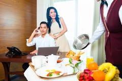Азиатская сервировка кельнера гостиничного сервиса в гостиничном номере Стоковое Изображение RF