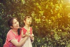 Азиатская симпатичная девушка и ее пузыри мыла матери дуя Семья на Стоковое Фото