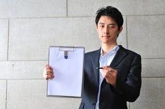 азиатская спрашивая подпись человека clipboard Стоковое фото RF