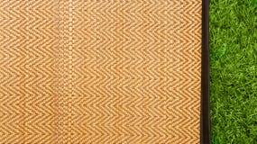 Азиатская сплетенная циновка древесины или ротанга на предпосылке текстуры зеленой травы Стоковые Изображения RF